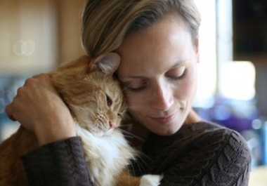 Woman snuggling with a cat